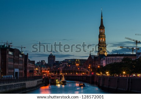 Boats sail on a canal in Hamburg with an long tower of a church raising above it all - stock photo