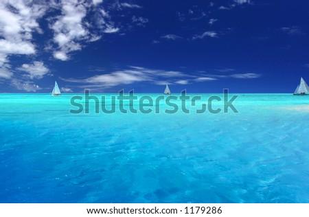 Boats sailing near tropical Motu - stock photo