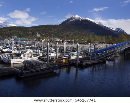 Boats ship at dock in small town with green mountains in background
