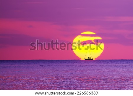 boats silhouette against the sun at sunset. Shot in Alghero, Sardinia - stock photo