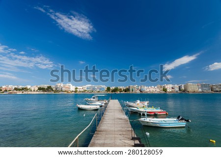 Boats tied at small harbour in Chalkida, Evia, Greece against a cloudy sky with the city buildings in the background - stock photo