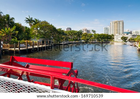Boats traverse the inland waterways of Fort Lauderdale, Florida. Tall buildings, luxury houses and trees frame the canal. - stock photo