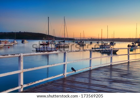 Boats, yachts and catamarans bob and tug at their moorings at sunrise, dreaming of places yet unvisited. Focus to foreground.  4 sec exposure   Hunters Bay NSW - stock photo