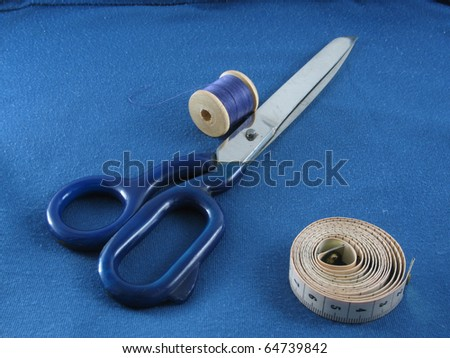 Bobbin of thread with scissors and measure tape - stock photo