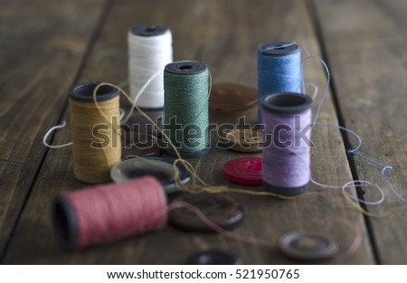 Bobbins with colorful threads on old wooden table background,