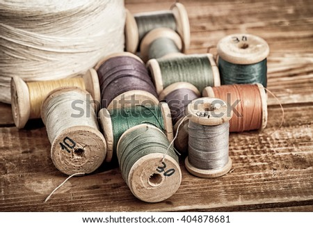 bobbins with thread and needles, striped fabric. Old sewing tools on the old wooden background.