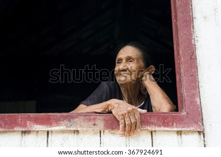 Boca de Valeria, December 03, 2015: Closeup view on one pleasure kind old mullato woman grandmother standing near window looking outdoor in white wooden house, horizontal picture - stock photo