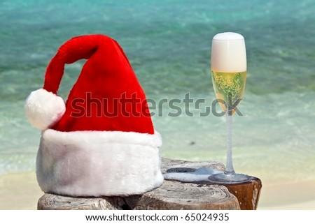 Bocal of champagne is on original  beach table is made from trunk of tree with Santa hat - stock photo