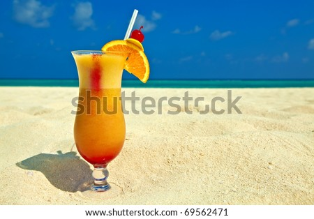 Bocal of fruity cocktail is on a sandy beach