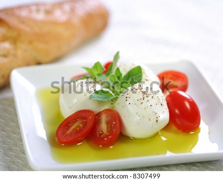 Bocconcini cheese with fresh baby tomato, olive oil and baguette bread - stock photo