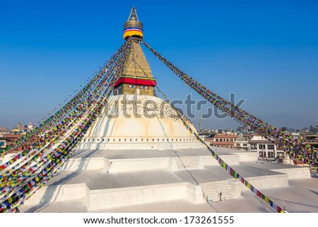 bodhnath stupa in kathmandu with buddha eyes and prayer flags with clear blue sky - stock photo