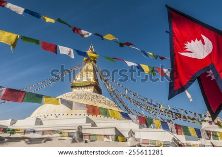 Bodhnath Stupa with Prayer Flags and Nepalese Flag, Kathmandu, Nepal. New brightly colored prayer flags have been hoisted for Losar (Tibetan New Year). On the right the Nepalese national flag. - stock photo