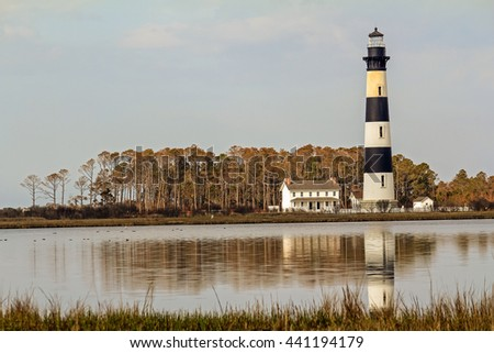 Bodie Lighthouse and support buildings reflecting in tide pool with trees in background and marsh weeds in foreground.  Taken on Cape Hatteras National Seashore, North Carolina Outer Banks.