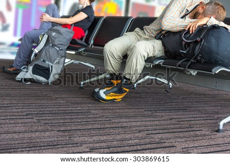 Bodies of people waiting airport terminal. Man and woman sitting at chairs waiting lounge airport building sleep on backpack informal sport dress code pants shirt luggage colorful interior background - stock photo