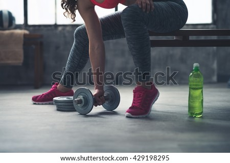 Body and mind workout in loft fitness studio. Closeup on fitness woman taking dumbbell from the floor in urban loft gym - stock photo