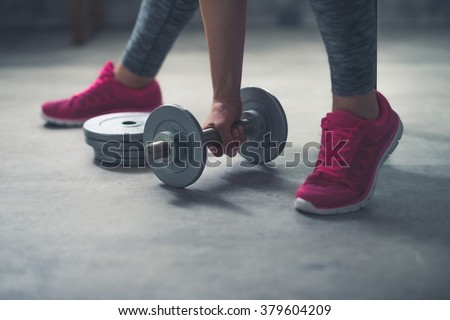 Body and mind workout in loft fitness studio. Closeup on woman lifting dumbbell from the floor - stock photo