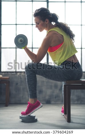 Body and mind workout in loft fitness studio. Fitness woman lifting dumbbell in loft gym