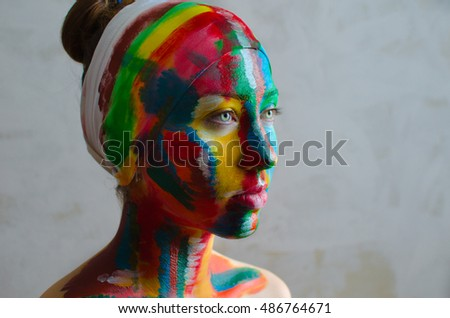 body art creative painting on face,artistic colorful portrait of a young beautiful model with face covered with thick paint