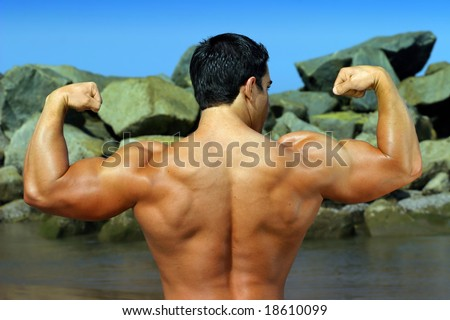 body builder flexing his back by the ocean with rocks in the background - full color photo - - stock photo