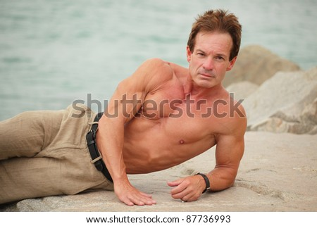 Body builder posing on the rocks - stock photo