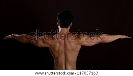 Body Builders back from tip to fingertip showing off his muscules - stock photo