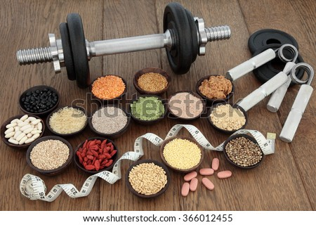 Body building equipment with dumbbells and hand grippers with health and super food  including supplement powders, ginseng vitamin pills, pulses, seeds, nuts, grains and tape measure.   - stock photo