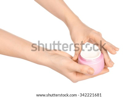 Body care and health topic: a woman's hand holding a pink jar of cream isolated on white background in studio - stock photo