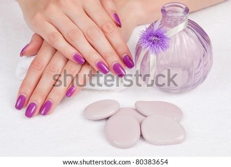 Body care: Magenta fingernails, lilac stones and vase - stock photo