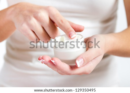 Body care. Woman applying cream on hands