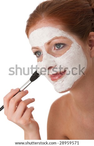 Body care - Young woman applying white facial mask using brush