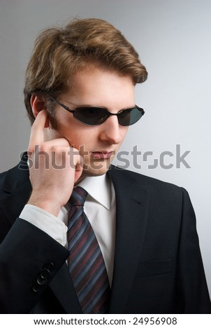 body guard or secret agent with serious expression on grey background - stock photo