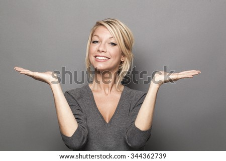 body language concept - satisfied 20s blond woman balancing something on both palms of her hands for equal choice of product,studio shot on gray background - stock photo