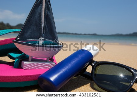 body lotion, pink flip flops and Sunglasses on the beach. - stock photo