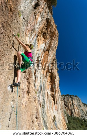 Body of female extreme Climber stepping up on high vertical Rock purposeful and sweeping Move Mountains View and Summer Sky on Background - stock photo
