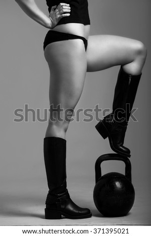 Body of one caucasian woman in black tshirt and shorts and black high shoes standing with one leg on kettlebell
