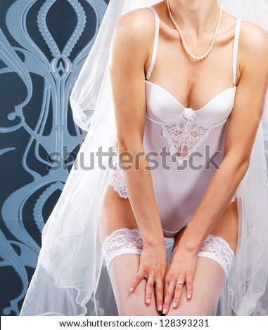 Body of sexy bride in lingerie over blue vintage background - stock photo