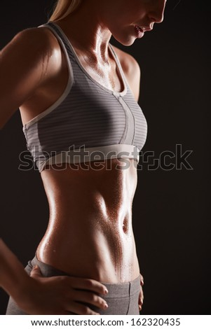Body of slim female in activewear standing in isolation - stock photo
