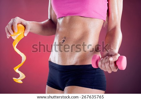 body of  woman with weights and orange - stock photo