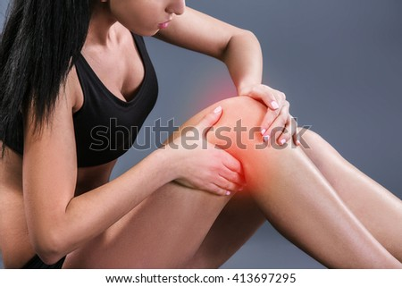 Body pain. Studio shot of beautiful young woman with dark brown hair. Woman suffering from knee pain. Red spot on knee - stock photo