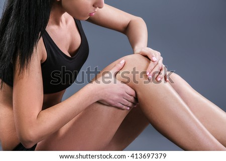 Body pain. Studio shot of beautiful young woman with dark brown hair. Woman suffering from knee pain - stock photo