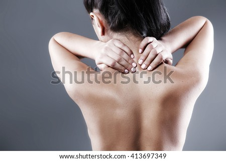 Body pain. Studio shot of beautiful young woman with dark brown hair. Woman suffering from neck ache - stock photo