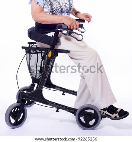 Body part of elderly woman sitting on a modern walker - stock photo