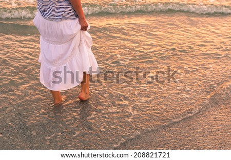 Body part outdoor portrait of a woman  in white cotton skirt walking along coastal line. - stock photo