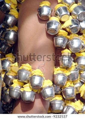 Body piercing of milk pot on Indian devotee's hand - stock photo