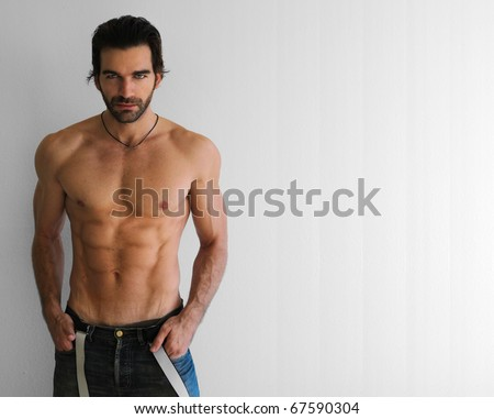 Body portrait of a sexy young man in jeans against neutral background - stock photo