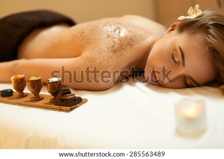 Body Scrub. Beautiful Blonde Gets a Salt Scrub Beauty Treatment in the spa Salon - stock photo