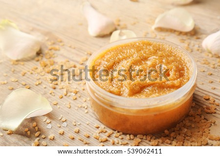 Body scrub, petals and sugar on wooden background