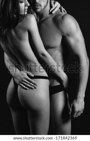 Body sexy couple on beach topless at sunset..Low light. - stock photo