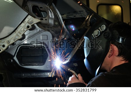 Body shop worker welding car panel.