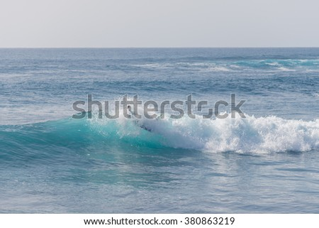 Bodyboarding and surfing in the waves of the Atlantic in front of the island La Gomera. A short light type of surfboard ridden in a prone position